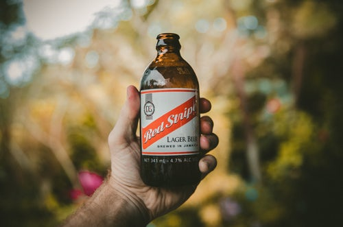 Bottle of red stripe beer held in a man's hand as one of Jamaica's favourite dishes
